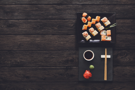 set free: Japanese food restaurant, sushi maki gunkan roll plate or platter set. Free, copy space, chopsticks, ginger and wasabi. Sushi at rustic wood background and black stone. Top view at black. Flat lay. Stock Photo