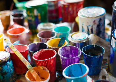 Multicolored plastic cans with paints.