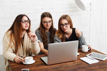 amigas conversando: Tres niñas trabajan y café con el ordenador portátil. chicas jóvenes amigos felices con el ordenador. Discusión, puesta en marcha, la conversación amistosa. Las mujeres amistad, la vida moderna, chismes y concepto de las citas por Internet.