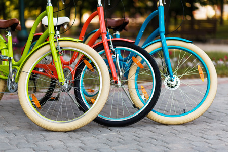 three wheel: Three beautiful city bright colored bicycles or bikes for woman standing in the summer park outdoors, wheel closeup Stock Photo