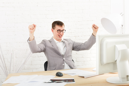 succesful: Winner businessman happy, succesful, in white modern office interior, sitting at computer table. Office worker in eye glasses, job in internet. High key, soft tone. Businessman win prize, gambling.