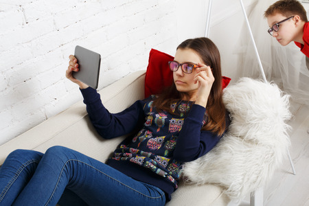 poor eyesight: Girl in eye glasses looks into tablet. Boy spies on her, tries to look into her tablet.