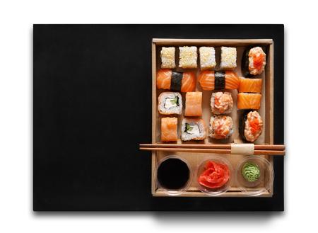 Japanisch-Food-Restaurant, Sushi maki gunkan Trecker oder Teller-Set. Stäbchen, Ingwer, Sojasauce, Wasabi. Sushi isoliert auf weißem Hintergrund und schwarzer Matte, zum mitnehmen, Lieferung Feld. Draufsicht. Lizenzfreie Bilder
