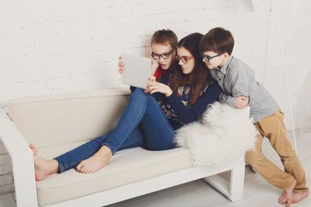 Grupo de niños en los vidrios del ojo mira en la tableta. Niños juegos de ordenador, redes sociales y los medios de comunicación el concepto de adicción.