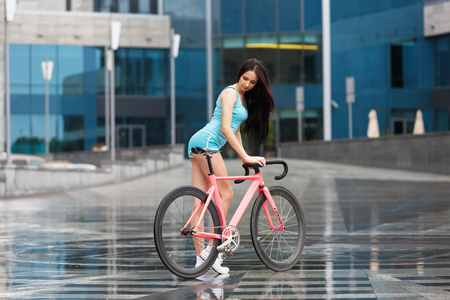 snickers: Sexy girl on bicycle. Young slim sexy sportive woman in blue shorts and white snickers long-haired, sensual posing on pink fix bicycle at grey background in urban city enviroment. Stock Photo
