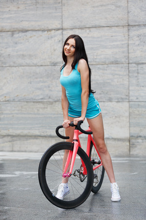 sexual activities: Sexy girl with bicycle. Young slim sexy sportive woman in blue shorts and white snickers long-haired, sensual posing with pink fix bicycle in urban city enviroment. Soft toned.