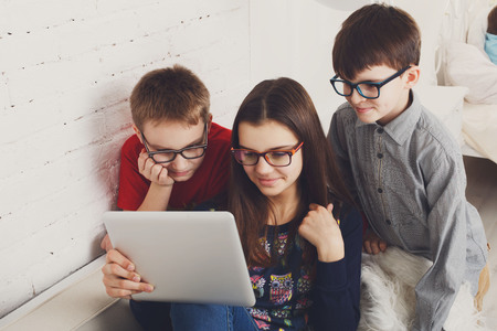 poor eyesight: Group of kids in eye glasses look into tablet. Children computer games, social networks and media addiction concept.