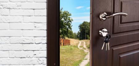 doorlock: Entrance door half opened to nature background. Stock Photo