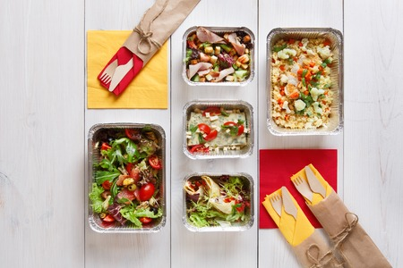 clean food take away in aluminium boxes with cutlery, vegetable salads and meat top view, flat lay at white wood background.