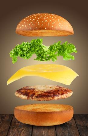 Cheeseburger del vuelo capas en el fondo marrón.