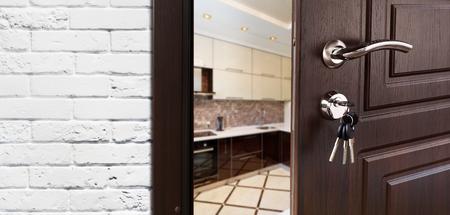 Half geopende deur naar een keuken. Deurklink, deurslot. Eetkamerdeur half open. Deur openen. Welkom concept. Toegang tot de kamer. Deur bij witte bakstenen muur, modern binnenlands ontwerp. Stockfoto
