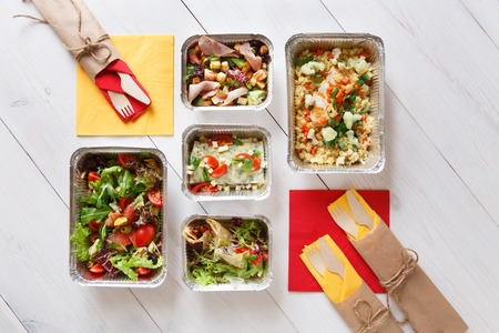 eat right: low carb food take away in aluminium boxes. Healthy food background. Salads and meat at white wooden table Stock Photo