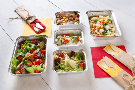 eat right: food take away in aluminium boxes, vegetable salads and meat at white wood. Stock Photo