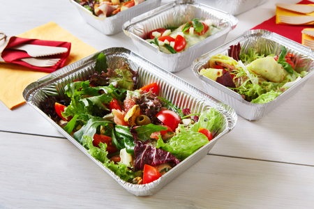 healthy food take away in aluminium boxes, vegetable salads and meat at white wooden table closeup