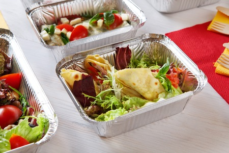 eat right: low carb food take away in aluminium boxes. Salads and meat at white wooden table