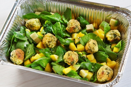 eat right: food take away in aluminium box. Falafel with mango cubes and spinach, closeup Stock Photo