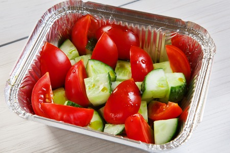 take away: food take away in aluminium box. Vegetable salad from tomatoes and cucumbers at white wood, closeup