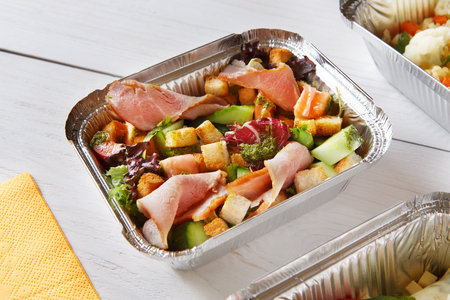 crouton: food take away in aluminium boxes. Vegetable salad with crouton and ham at white wooden table Stock Photo
