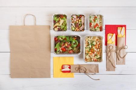 comidas saludables: alimentos saludables, nutrición de la aptitud para llevar en cajas de aluminio, cubiertos y el paquete, vista desde arriba, en posición plana en madera blanca Foto de archivo