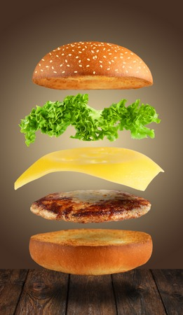 Cheeseburger flying layers at brown background. Reklamní fotografie