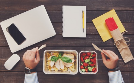 hand lay: food take away in aluminium boxes: roasted turkey with salad. Cell phone, mobile, fitness bracelet on hand. Top view, flat lay