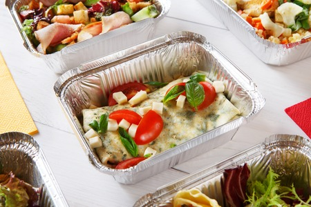 eat right: food take away in aluminium boxes. Vegetables and french crepe with cheese at white wood Stock Photo