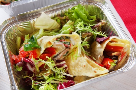 eat right: low carb food take away in aluminium container. Vegetable salad with crepe closeup at white wooden table