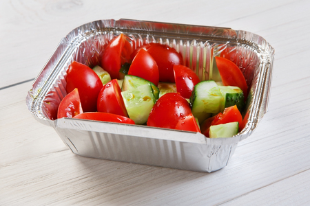 eat right: Vegetable salad from tomatoes and cucumbers at white wood, closeup