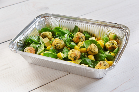 eat right: food take away in aluminium box. Falafel with mango cubes and spinach at white wood
