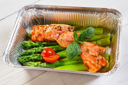eat right: food take away in aluminium box. Grilled salmon steak with asparagus and cherry tomato