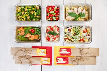 eat right: food take away in aluminium boxes with cutlery, vegetable salads and salmon top view, flat lay at white wood background.