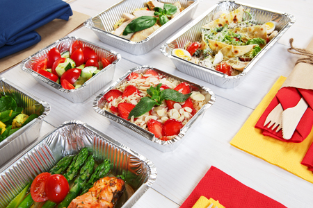 eat right: healthy food take away in aluminium boxes and bag, vegetables and salmon closeup