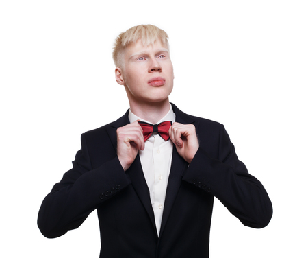 Blond albino guy in suit with red bow tie isolated at white background.