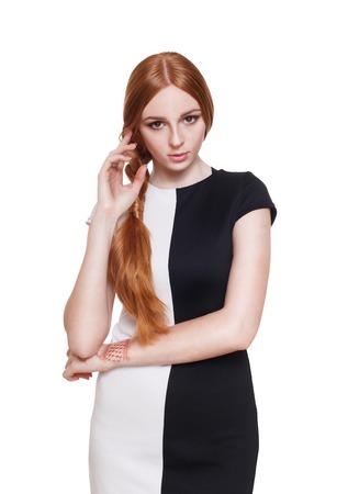 Portret van een mooie roodharige vrouw in elegante zwarte en witte jurk. Stockfoto - 58115738