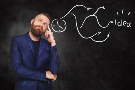 consider: Man thinking of new idea decision. Young man thoughtful for siolution, drawings at black gradient background with arrows, idea, brain storm concept. Stylish guy with beard consider plan.