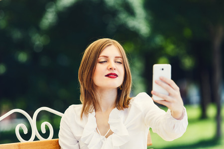 narcissistic: Selfie making. Girl or young woman in white blouse makes selfie with tablet. Woman with tablet sitting on the bench in the park. Young woman student makes photo for internet, instagram.