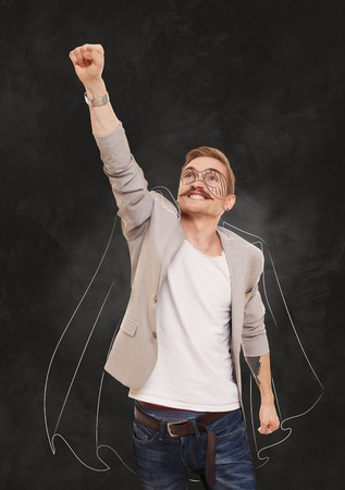 achievment: Man in superhero pose doing fly gesture. Imaginary superman, super hero costume drawing at black gradient background. Young man shows flying pose, achievment, success, power, strong guy concept.