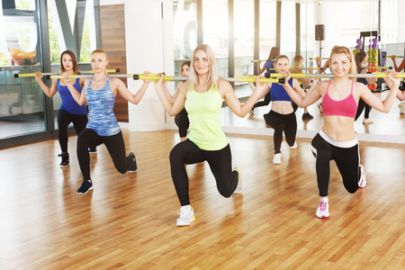 lunges: Group of young women in fitness class. Group of people making exercises. Girls do lunges with barbells. Healthy lifestyle, training, sport, gym studio. Girls in fitness club, lunges with weights.