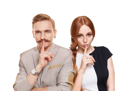 mystery man: Woman and man keep secret. Couple shows hush sign, adultery, relationship issue, marriage cheating concept. Secret love, jealousy. Mystery, privacy, intimacy. Young beautiful couple isolated at white Stock Photo