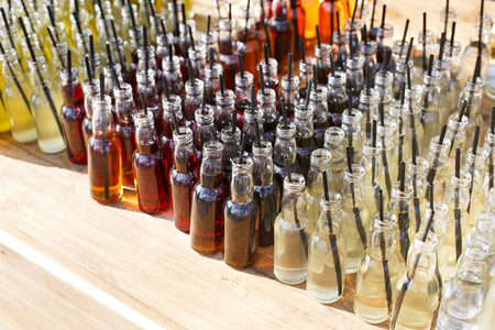 shooter drink: Alcohol cocktails, shots in glass bottles. Row of many alcohol tasty shots with straws in small bottles. Creative cocktails. Unusual alcohol in bar, many, plenty of drinks for party., catering, event