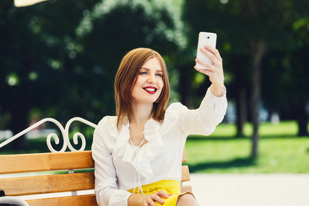 conceited: Selfie making. Girl or young woman in white blouse makes selfie with tablet. Woman with tablet sitting on the bench in the park. Young woman student makes photo for internet, instagram.