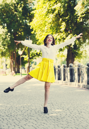 Happy young girl dancing in the park. Happy woman dance outdoors in summertime. Young slim student girl in the park cheerful and positive, emotional, shows her good mood.