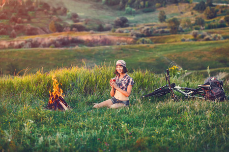 travel mug: Girl near bonfire. Travel, bicycle tourism, camping - young slim sporty woman tourist brunette at the beautiful nature landscape sitting near the tent by the fire. Girl with drink in mug in her hands. Stock Photo