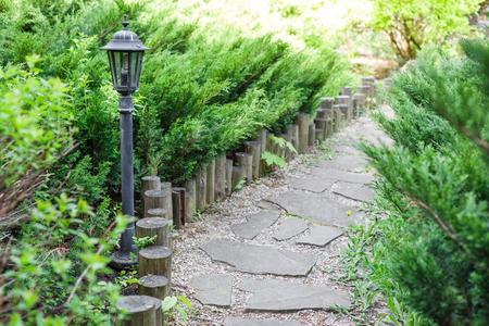 flower garden path: Beautiful landscape design, garden path tiles closeup with park light, wooden fence, evergreen bushes and shrubs in sunlight. Modern landscaping. Summer garden or park design.