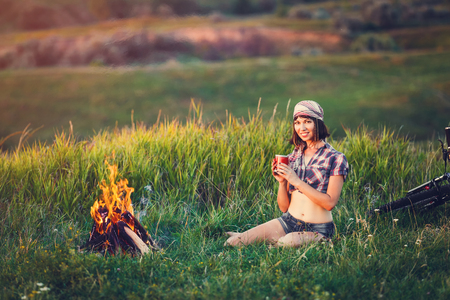 travel mug: Girl near bonfire. Travel, tourism, camping - young slim sporty woman tourist brunette at the beautiful nature landscape sitting near the tent by the fire. Girl with drink in mug in her hands.