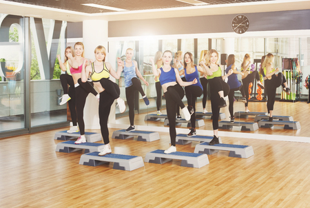 aerobic exercise: Group of young women in fitness class do step aerobics. Group of people making exercises. Girls at step. Healthy lifestyle, training, sport, gym studio. Girls in fitness club, leg kicks