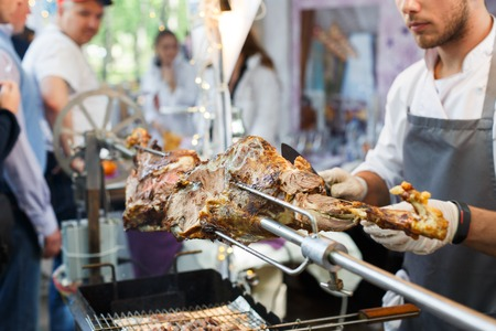 Meat barbecue picnic at country fair. Lamb leg roasted at spit. Lamb grill, big piece of meat at rolling skewer. Street vendor, professional Chef cooking food bbq, unrecognizable. Cooking, catering Stock Photo