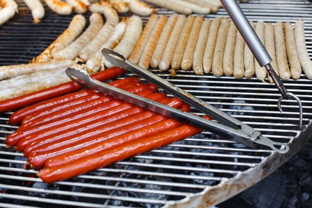 grill tongs sausage: Sausage party. Barbecue large grill outdoors. Cookout bbq food. Big roasted pork and beef german sausages, white polish kielbasa. Meat grilled snack. Street food, fast food. Sausages with metal tongs