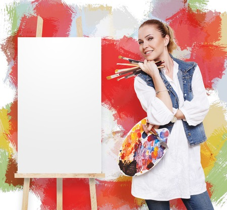 fine art: Woman artist with art tools. Female painter with brushes and palette stands by empty canvas at easel near colorful wall with copy space. Fine art school. Art classes for adults, education concept.
