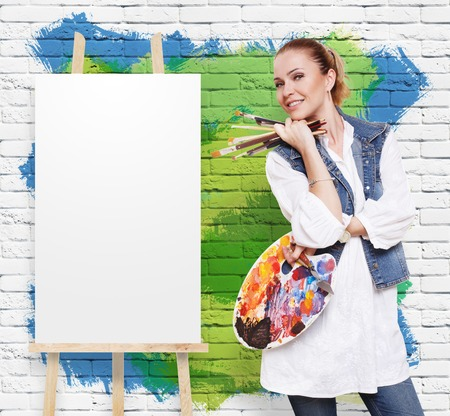 fine art: Art and craft. Woman artist with art tools. Girl painter with brushes and palette. Empty canvas at easel at colorful brick wall with copy space. Fine art. Art classes for adults, education concept. Stock Photo